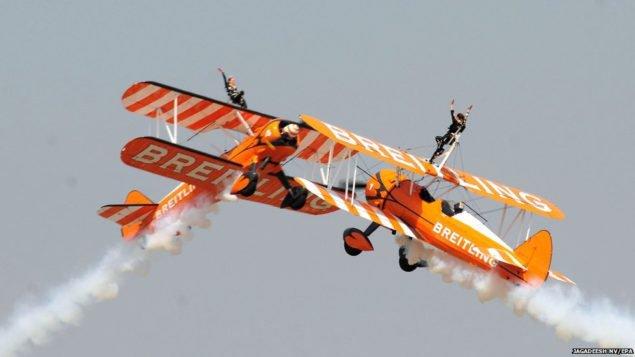 """Пилоты на """"Боенгах Стирман"""", бипланах, во время пилотажа на выставке в Aero India 2015 шоу в Yelahanka авиабазы в Бангалоре"""