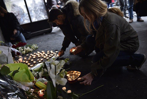 People place flowers and candles outside the cafe 'La Belle Equipe' at the Rue de Charonne in Paris on November 14, 2015, following a series of coordinated attacks in and around Paris late Friday. At least 128 people were killed in the Paris attacks on the evening of November 13, with 180 people injured, 80 of them seriously, police sources told AFP. AFP PHOTO / LOIC VENANCE        (Photo credit should read LOIC VENANCE/AFP/Getty Images)