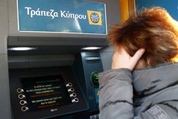 epa03629400 A woman   attempts to withdraw from an ATM in the centre of Athens only to find the machine is out of service,  17 March 2013. It appears that the sudden Bank crisis in Cyprus has also affected the Greek depositors.  EPA/KATIA CHRISTODOULOU