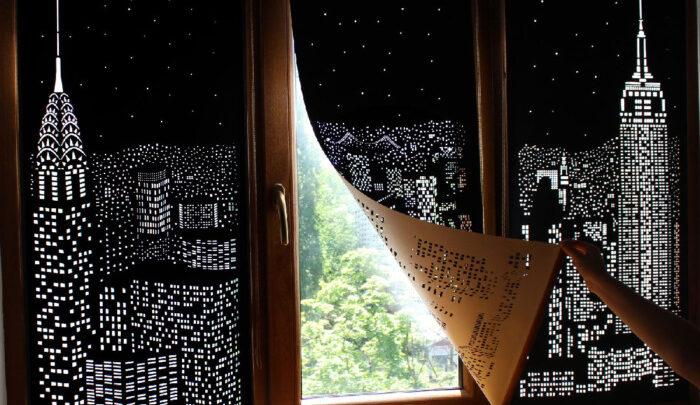 Будинки і зірки, вирізані в темних фіранках, перетворюють вікна в нічні міські пейзажі